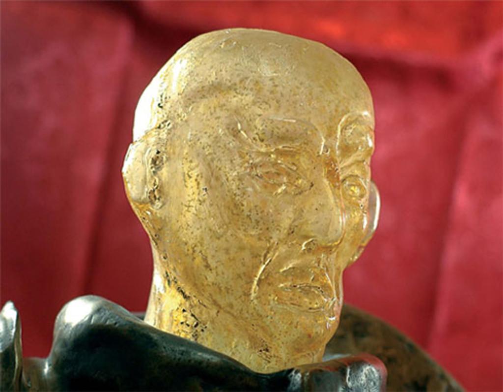 Scultura di testa virile in vetro soffiato ambra e oro montata su bronzo.